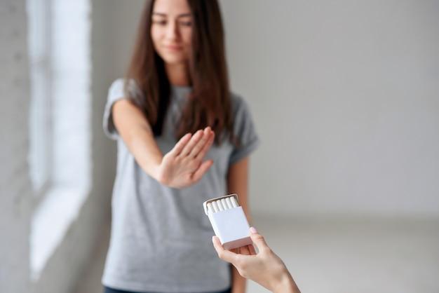Здоровая молодая красивая женщина отказывается принимать сигарету из пакета
