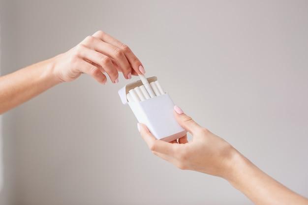 Крупным планом женщина держит сигарету пачку и предлагает сигарету другому лицу