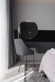 高級マンションのモダンなグレーの寝室で女性のメイクアップ用のテーブルとミラー