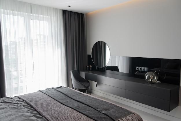 高級マンションのモダンなグレーの寝室で女性のメイクアップテーブル