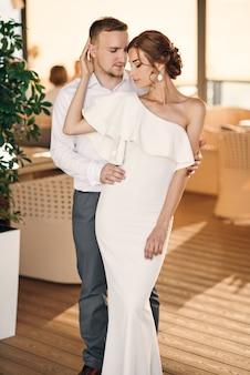 Красивый жених нежно обнимает свою красивую чувственную невесту в белом платье на террасе