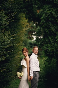 官能的な美しい花嫁とハンサムな新郎がお互いに戻って横になっています。
