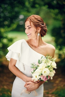 白いドレスを着た見事な花嫁と彼女の手で花束が優しい笑顔