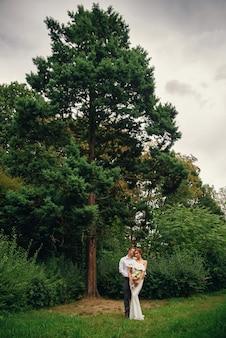Стильная милая пара в теплых объятиях под елкой в парке
