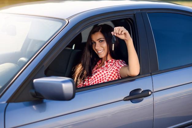 Красивая брюнетка женщина за рулем дорогой машины