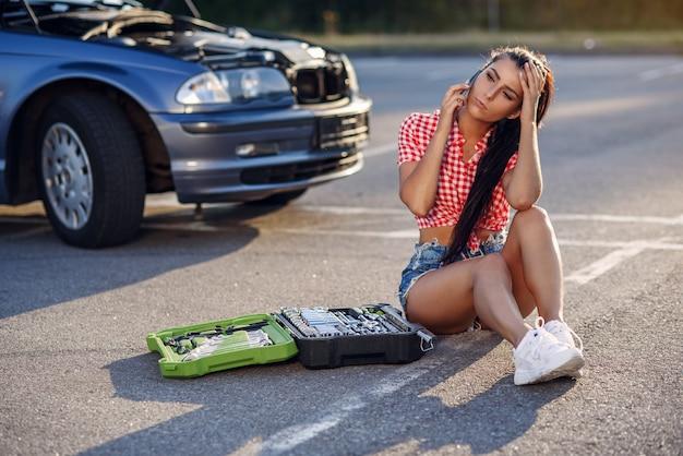壊れた車の近くに座っている女性を強調しました。