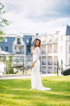 Привлекательная очаровательная невеста в белом кружевном платье на зеленой траве