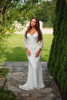 Привлекательная очаровательная невеста в белом кружевном платье с зеленой травой