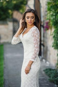 Великолепная очаровательная невеста в белом кружевном платье во дворе замка