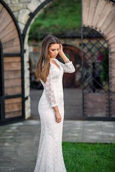 Великолепная очаровательная сексуальная невеста в белом кружевном платье на кованой двери во дворе замка