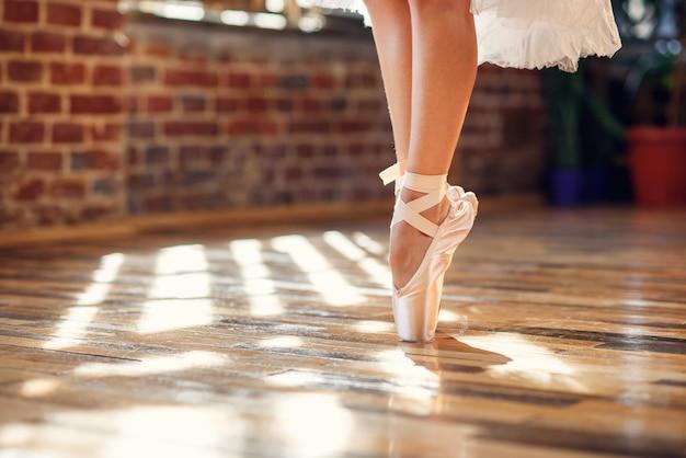 ダンスホールで白いポワントバレエシューズを着てバレリーナのクローズアップダンス脚。