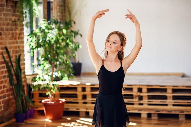 Молодая балерина в черной пачке практикующих танцевальные движения.