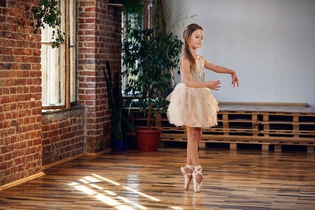Юная балерина в балетной пачке и балетных туфлях отрабатывает танцевальные движения в танцевальном зале.