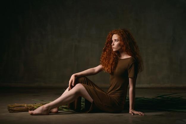 カーキ色のドレスで乾燥した杖に座っている赤い巻き毛の少女