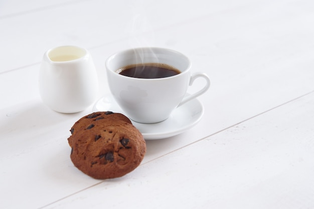 ミルクとクッキーの香り豊かなコーヒーのカップ。チョコレートのスライスと白いコーヒーカップのショートブレッドクッキー。