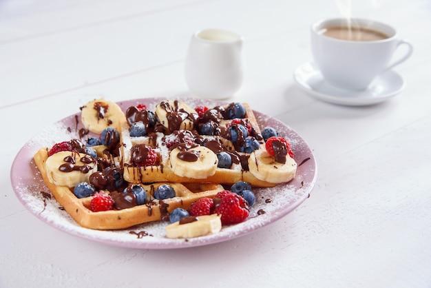 一杯のコーヒーとブルーベリー、ラズベリー、バナナ、砂糖の粉が入ったおいしいベルギーワッフルには、液体チョコレートが入っています。