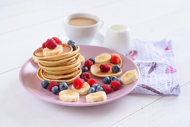 バイオレットプレートで新鮮な果実とおいしい自家製パンケーキラズベリー、ブルーベリー、バナナのパンケーキのおいしい健康的な朝食。ミルク入りのアロマコーヒー。