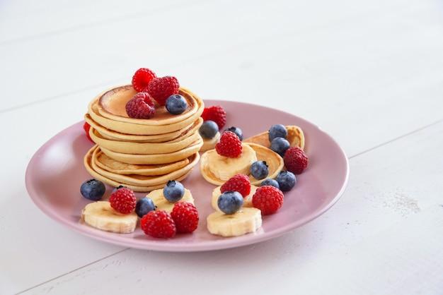 Вкусные домашние блины со свежими ягодами в фиолетовой тарелке вкусный и полезный завтрак из блинов с малиной, черникой и бананами.