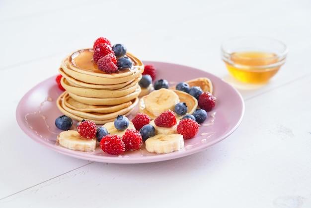 Вкусные домашние блины со свежими ягодами в фиолетовой тарелке вкусный и полезный завтрак из блинов с малиной, черникой и медом.
