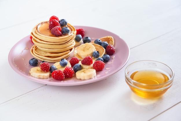 バイオレットプレートで新鮮な果実とおいしい自家製パンケーキラズベリー、ブルーベリー、蜂蜜とパンケーキのおいしい健康的な朝食。