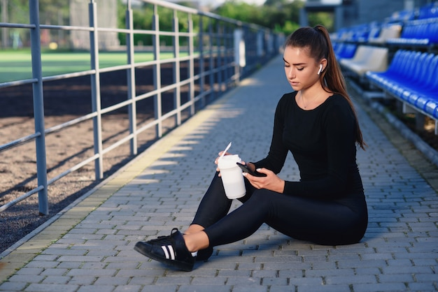 黒いスポーツウェアの美しいフィットネス女性は、白いボトルからスポーツ栄養を飲み、トレーニング後にスタジアムトリビューンで電話を使用します。スポーツと健康の概念。