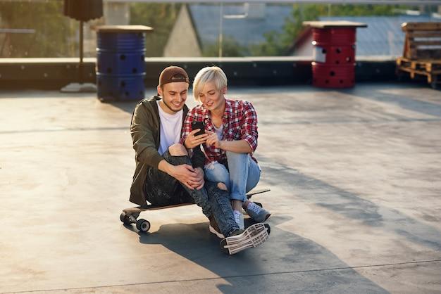 工業ビルの屋上遊び場でロングボードスケートボードの上に座って、電話を使用してハンサムなスタイリッシュなカップル。現代都市のアクティブなライフスタイルコンセプト。