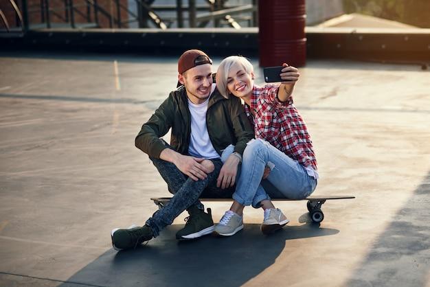 工業ビルの屋上でロングボードスケートボードに座って、電話で自己写真を撮るハンサムな若いカップル。現代都市のアクティブなライフスタイルコンセプト。