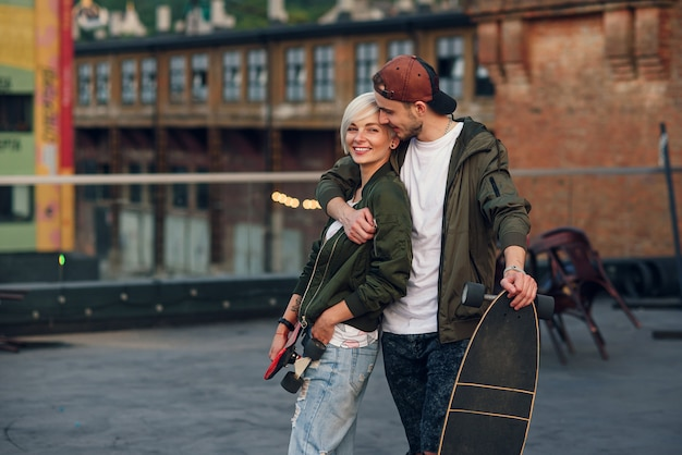 Молодая очаровательная влюбленная пара, идущая со скейтбордами на крыше промышленного здания на закате.
