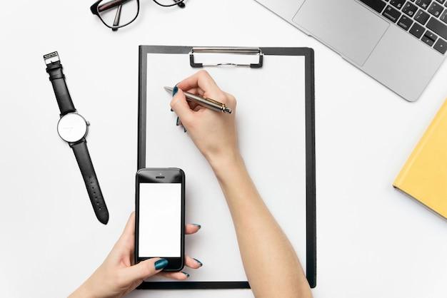 女性の手はペンを持ち、きれいな紙に書きます。ラップトップ、電話、用品を備えた白いオフィスデスク。