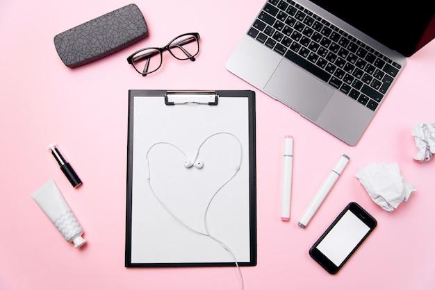 オフィス愛の概念。ハートのようにレイアウトされたヘッドフォン付きの女性のピンクのオフィスデスク。ノートパソコン、空白の白い画面、クリーム、口紅、眼鏡、消耗品と電話で女性の職場。