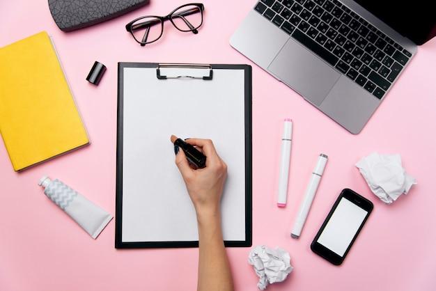 女性のピンクのラップトップ、白い画面、眼鏡、口紅、クリーム、しわくちゃの紙のボールとオフィスデスクの平面図。女性の手は、紙の背景の白いシートに口紅を書き込みます。