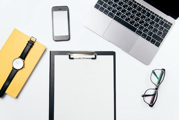 ノートパソコン、携帯電話、ノートブック、トップビューホワイトオフィスデスク、無料コピースペースと消耗品、フラットレイアウトの背景を持つ紙の空白