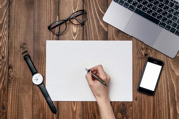 女性の手は白い紙にペンを書きます。木製のオフィスデスクテーブルノートパソコン、携帯電話、クリアホワイトペーパー、オフィス用品の背景