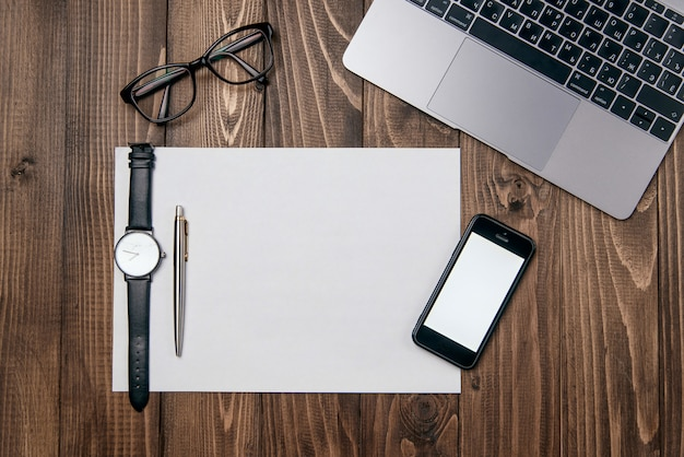 ノートパソコン、携帯電話、クリアホワイトペーパー、オフィスの木製オフィスデスクテーブルは背景を提供します。