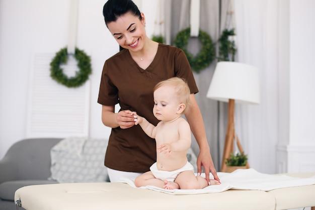 プロの女性マッサージ師とマッサージをしている少し面白い赤ちゃん。モダンで居心地の良い部屋のソファでの子供のマッサージ。親切で優しい子供の医者。
