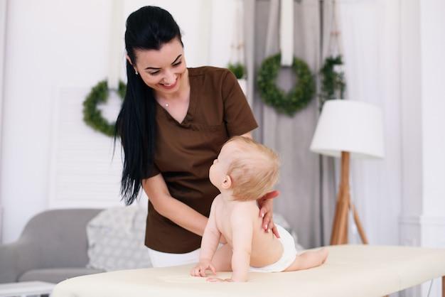 プロの女性マッサージ師が小さな赤ちゃんにマッサージをします。モダンで居心地の良い部屋のソファでの子供のマッサージ。