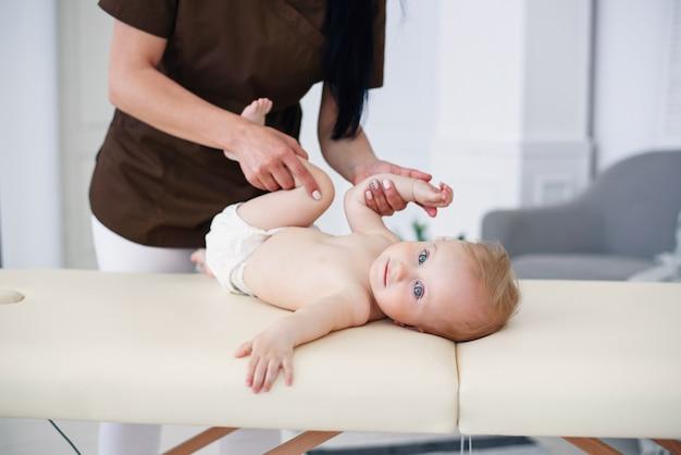 健康管理と医療のコンセプト。プロの女性マッサージ師は、モダンで居心地の良い部屋で小さな赤ちゃんにマッサージと体操を行います。