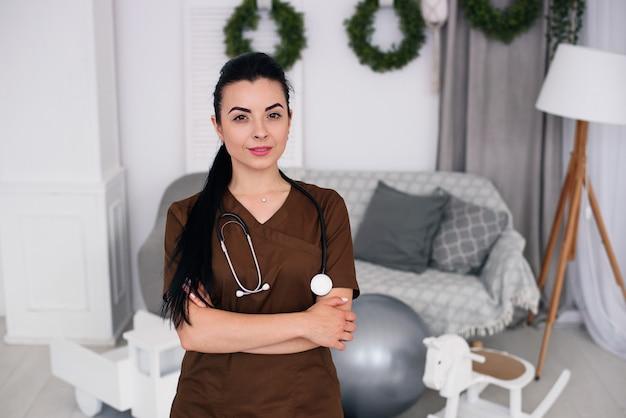 茶色の医療用ローブを着て聴診器で笑顔の優しい子供の医者の女性。健康管理と医療のコンセプト。