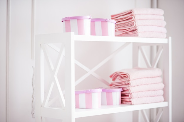 白い棚の上のアクセサリーときれいなピンクのタオル用の女性用ボックス。浴室に女性のアクセサリーが付いている棚。
