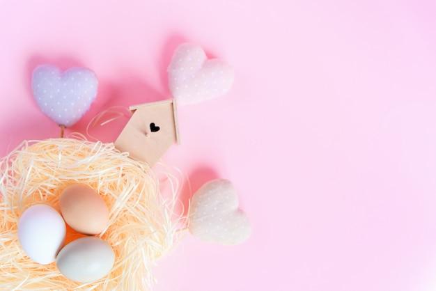 わらの巣、木製の鳥の送り装置、ピンクの背景に装飾的な繊維の心の異なる色のイースターエッグ、