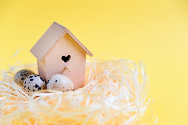 わらの巣にウズラの卵、黄色の表面に木製の鳥の餌箱。無料のコピースペース。イースターのコンセプト。