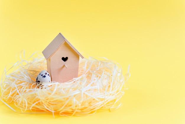 わらの巣、黄色の背景に木製の鳥の送り装置でウズラの卵。無料のコピースペース。イースターのコンセプト。