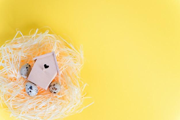 わらの巣、黄色の背景に木製の鳥の送り装置でウズラの卵。イースターのコンセプト。