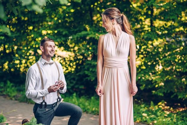 若い男は彼の最愛の少女の前で片膝立ち、彼女に彼の妻になることを提案します
