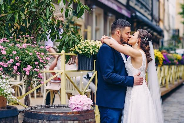 外に立っている見事な結婚式のカップルの優しいキス
