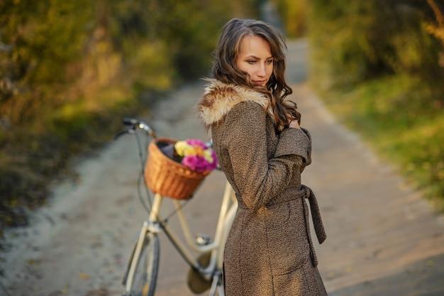 花でいっぱいのバスケットを持つ女性自転車の近くに立っている秋のコートで美しい少女