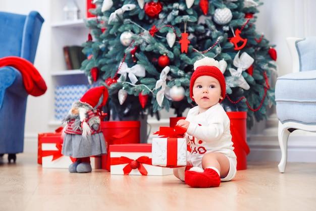 魅力的な幼児男の子はクリスマスギフトボックスを保持しています。クリスマス休暇の概念。