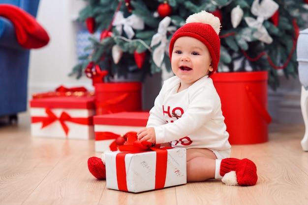 魅力的な幼児の少年は、赤いリボンと白いクリスマスギフトボックスを保持しています。クリスマスの装飾が施された部屋でお祝い服を着て面白いかわいい赤ちゃん。クリスマスと新年の休日の概念。