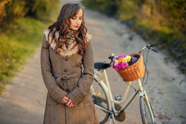 バスケットの花を持つ女性の自転車の近くに立っている秋のコートで美しい少女。