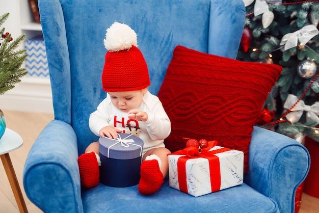 クリスマス服の美しい小さな男の子は青い大きな椅子に座って、彼の手でギフトボックスを保持しています。